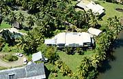 aerial view showing relation of Villa to canal, marina(by flagpole but hidden by coconuts), swimming pool and tennis court..